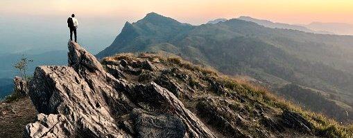 businessman hike on the peak of rocks mountain at sunset