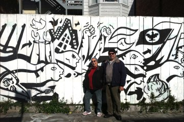 Muralist Chuy Campusano's (1945 - 1997) sister Lorenza Camplis and her husband Carlos Camplis in front of Chuy's mural he painted in 1994.