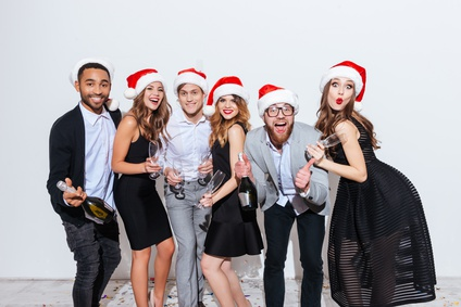 Group of cheerful young friends in santa claus hats holding bottle of champagne and glasses over white background