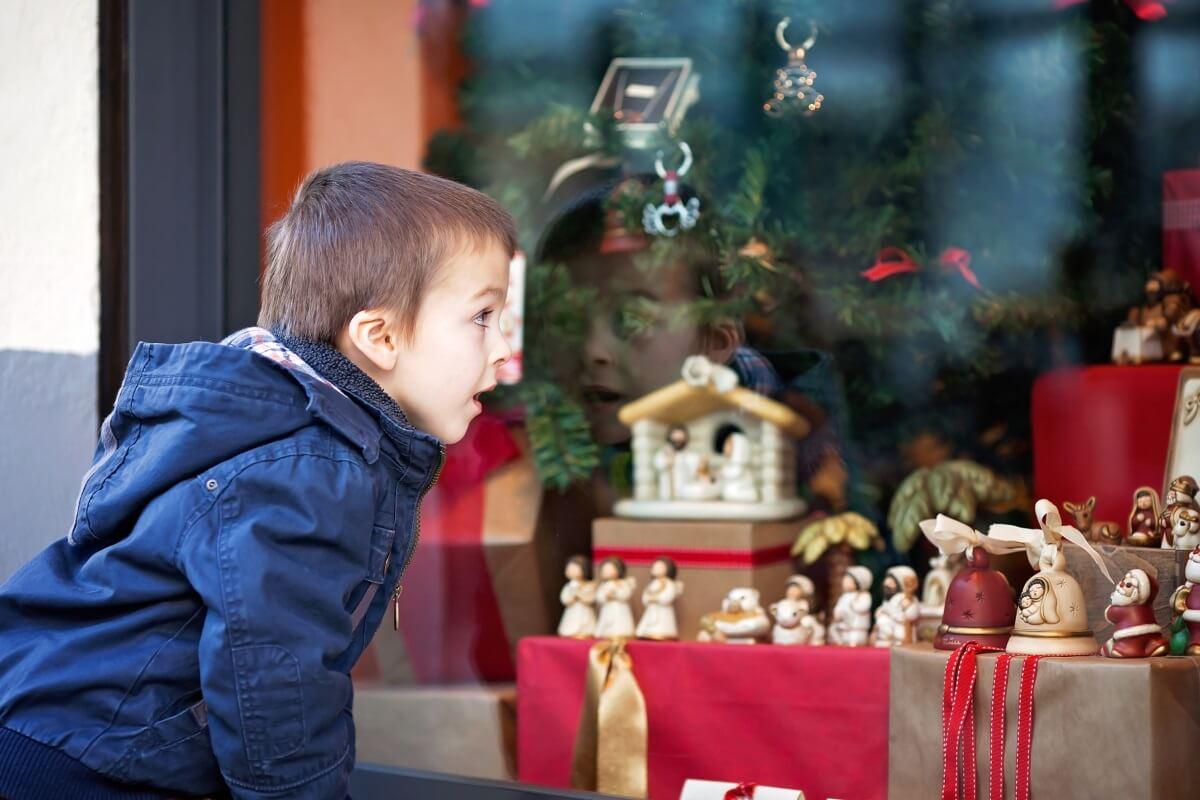Sweet little boy, looking through a window in shop