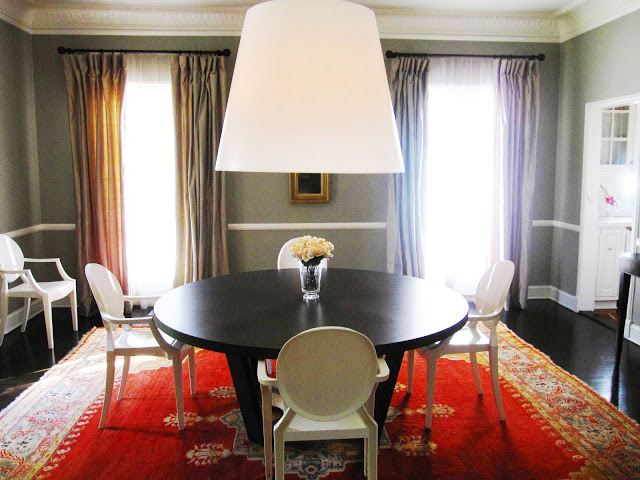 philipe starck's dining room in los angeles with giant pendant light hanging, gray walls, red carpet and louis chairs