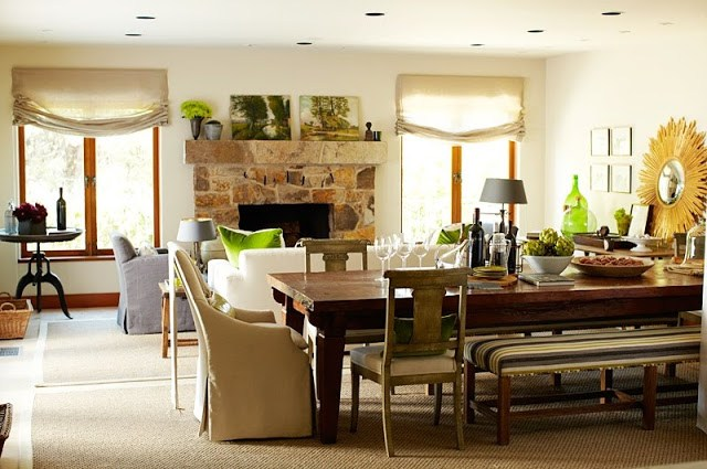 great room with stone fireplace, long wooden table with a variety of chairs ranging from an arm chair to a bench surrounding it