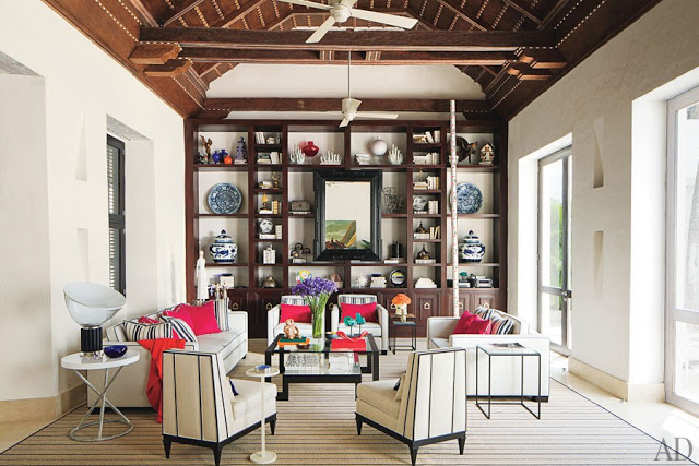 richard mishaan's cartagena, colombia living room with built in book shelf, high ceilings with exposed beams, patterson flynn martin carpet rug, donghia side table, white sofas with pink accent pillows and matching side chairs