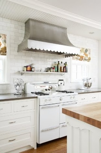 close up of rehkamp larson architects' vintage kitchen with a roper stove, a scalloped metal hood with subway tiles from counter to ceiling in the backsplash, the countertops are black and the cabinets under them are white.