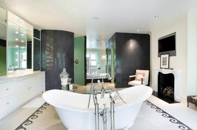 master bathroom with tile floor, stand alone tub, fireplace, green walls and a tv