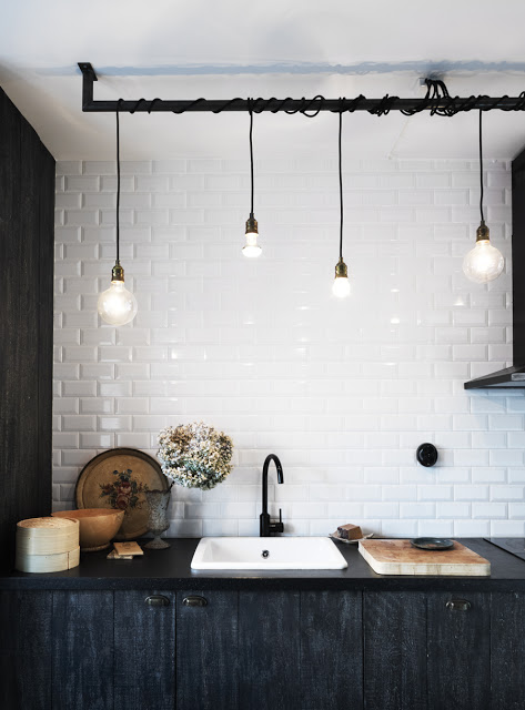 pendant lights over a sink with dark wood cabinets and counter