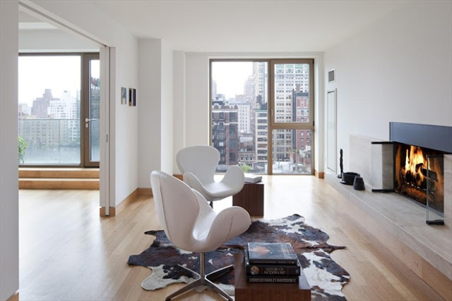 fireplace room in a New York City apartment with light wood floors, a cow skin rug, two white chairs and a great view of the city