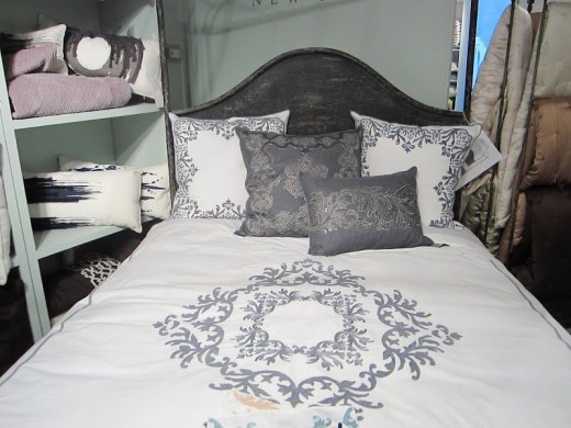 Bed with wood headboard stained dark grey and embroidered bedding with crystal beads from Ankasa