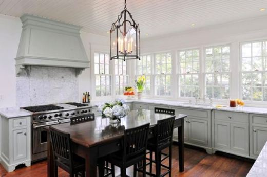 Alternative view of the kitchen's grey cabinets, marble counter tops, casement windows, stained oak table dining room table surrounded by matching chairs and a chandelier