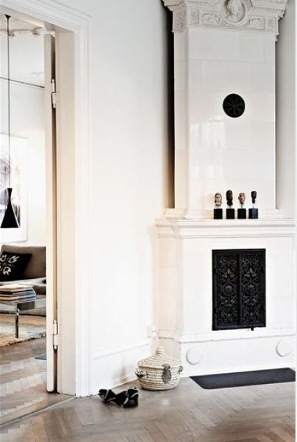 fireplace with white tile and a wood herringbone floor