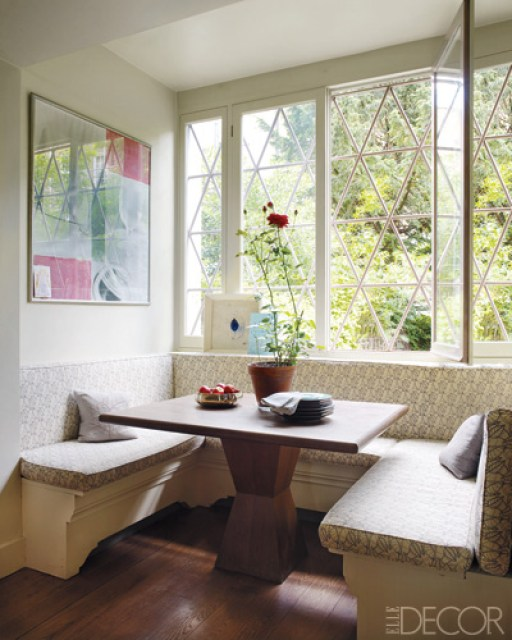 elle decor's allegra hicks' breakfast nook with banquette seating with patterned cushions, a wodden table and diamond windows with a view of a backyard