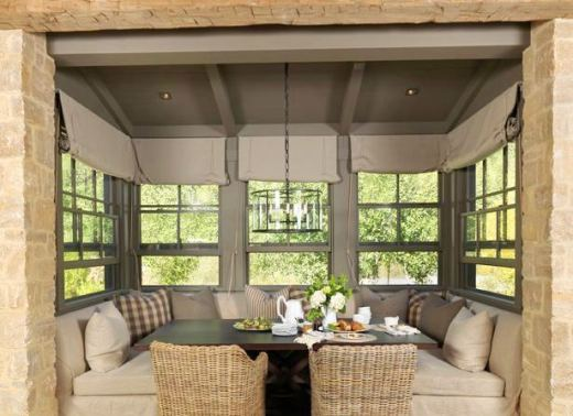 Rustic breakfast nook with built in banquet seating with two wicker chairs, casement windows with roll up shades, a dark wood table, a stone wall and a pendant light