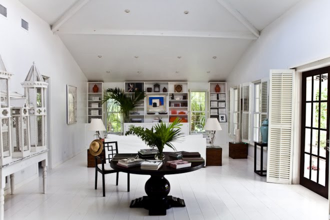 White living room with painted wood floor, exposed beams, white built in bookshelves, Moroccan lanterns, and a round dark wood table and chair