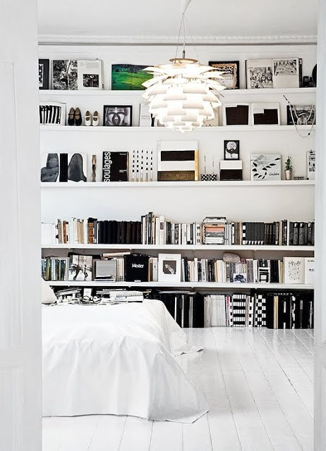 emmas blogg se's black and white bedroom with floating books display, low bed, white wood floor and a large flower lamp
