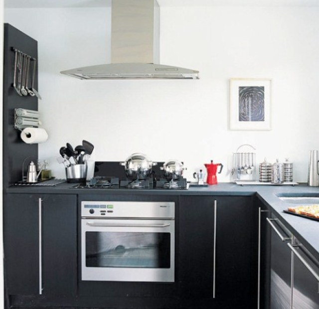 Small kitchen with dark oak cabinets and black poured synthetic cement like counters