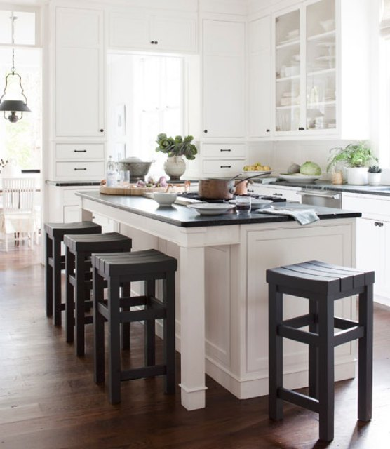 Kitchen with white cabinetry, dark green soapstone counters with a matching island and dark wood stools