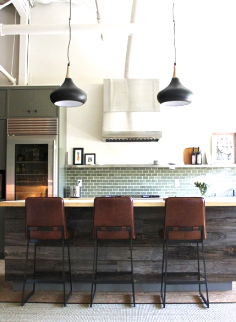 wine country home designed by Krista Schrock and David John Dick with reclaimed wood paneled kitchen island, black pendant lights, leather barstools and green subway tile backsplash