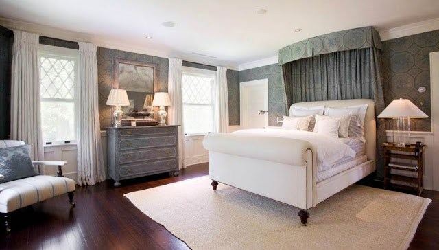 Master bedroom with fabric upholstered walls and a sleigh bed, rustic chest of drawers and night stand and a dark wood floor