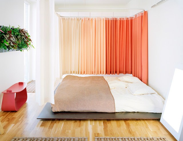bedroom with orange floor length curtains, a low bed, light wood floor, and a red accent table
