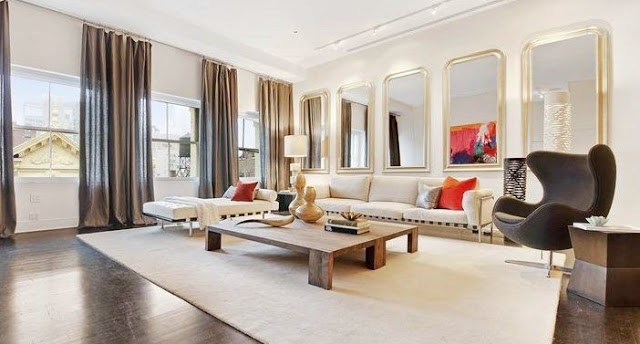 living room in a Soho Condo in New York with white sofa, gray table, decorative mirrors, gray floor length curtains, and orange accents