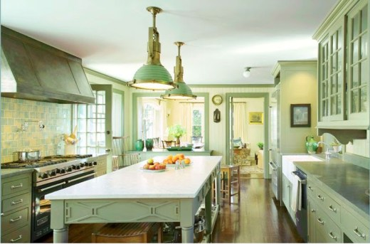 Traditional ktchen by Michael S. Smith with green and yellow backsplash, green cabinets and drawers, an island under two pendant lights and a hardwood floor