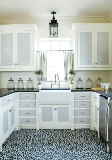 Kitchen in a pool house with a pebble floor, blue and white cabinets and drawers, stainless appliances and a small pedant light