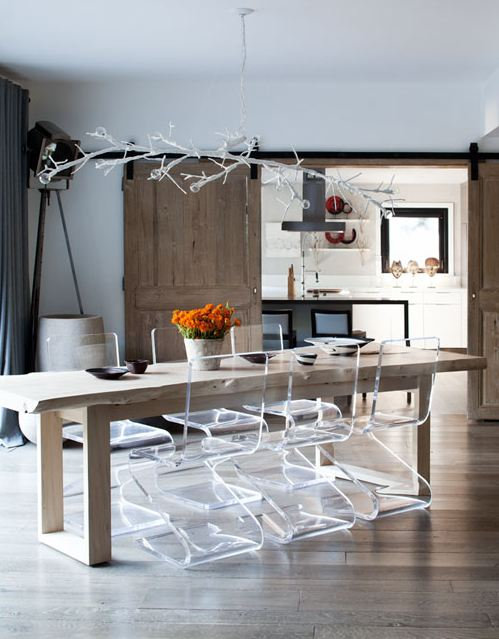 Dining room with clear lucite chairs, a long, thin, reclaimed wood farmhouse style dining table and a modern chandelier in the shape of a branch with wood sliding doors leading to the kitchen