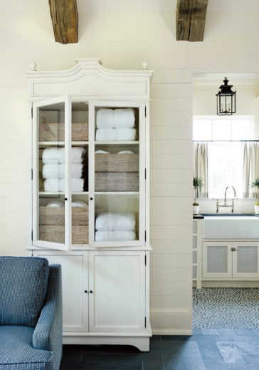 Close up of a white cabinet in a pool house with glass door