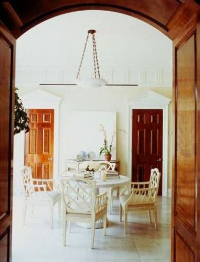 Foyer by Michael S. Smith with white fretwork chairs around a white pedestal round table under a white pendant light, tile floor and two wood doors made of different kinds of wood