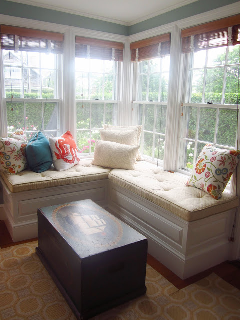 window bench with accent pillows, a wooden chest with a ship painted on it and a yellow rug