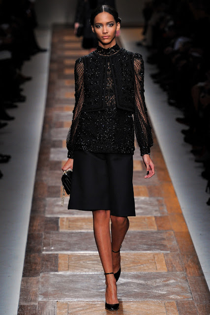 model from valentino fall 2012 runway show wearing a sparkly black top and black culotte long shorts