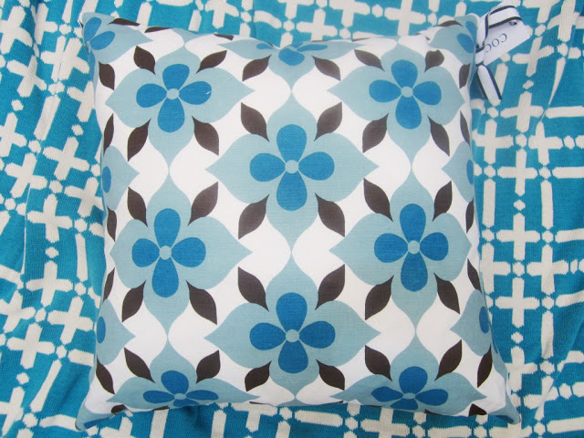 COCOCOZY Coco's Flower cotton pillow in blue and brown on a peacock blue COCOCOZY Plaid Solid Throw