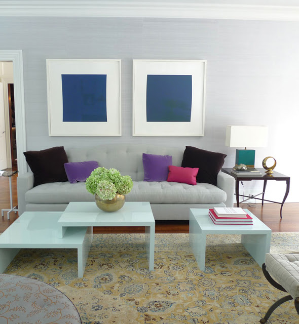 frank roop color blocked living room with purple, pink and brown pillows on a neutral sofa, two framed blue squares hang above it in a white room with wood floors, white coffee tables and yellow patterned rug