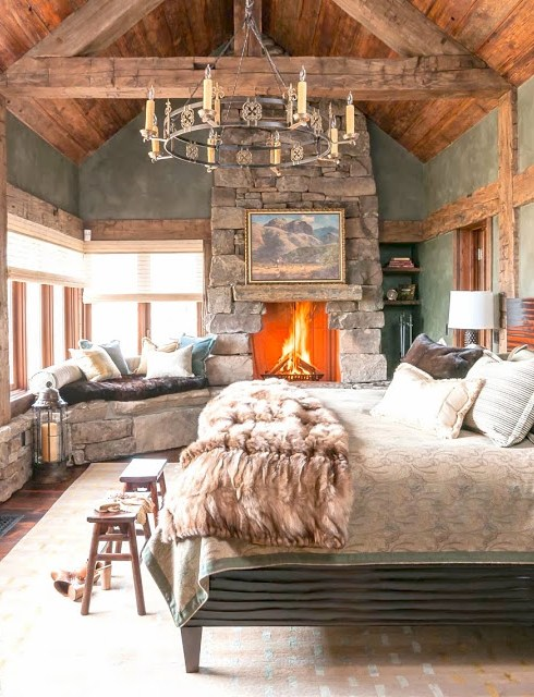 Luxurious cabin inspired bedroom with a stone fireplace, fur throw and a window seat