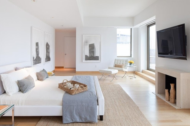 master bedroom in an New York City apartment with a fireplace, flat screen view, white walls, white bed with gray accents