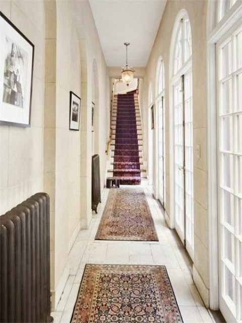 Hallway in a NYC home with french doors, white washed wood floors and Persian rugs