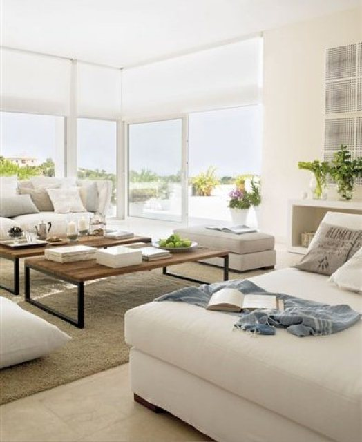 Living room with wrap around floor to ceiling sliding glass doors, dueling sofas and wood coffee table on a shag rug