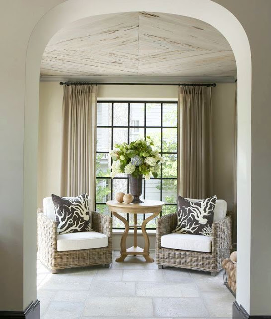 Wicker chairs in a sitting area in front of window with black trim with a large bouquet of hydrangeas in a vase on a round wooden table