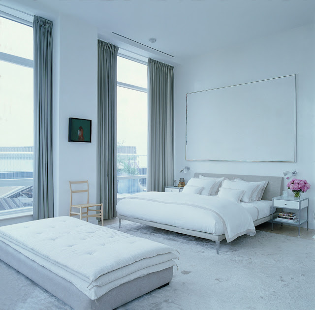 modern grey and white bedroom with upholstered headboard, large windows with floor length curtains and a long ottoman