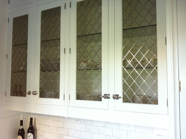 Kitchen with glass upper cabinets with metal cage detailing