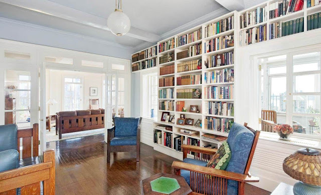 study and home office with built in bookcase full of books, wooden chairs with blue patterned cushions, a pendant light and wood floors