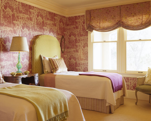 Twin bedroom with pink toile wallpaper, super tall, green and white poka doted upholstered headboards, large window with patterned pull up curtains