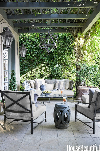 Neutral outdoor patio by Mary McDonald modern lighting grey sofa and armchairs Chinese garden stool