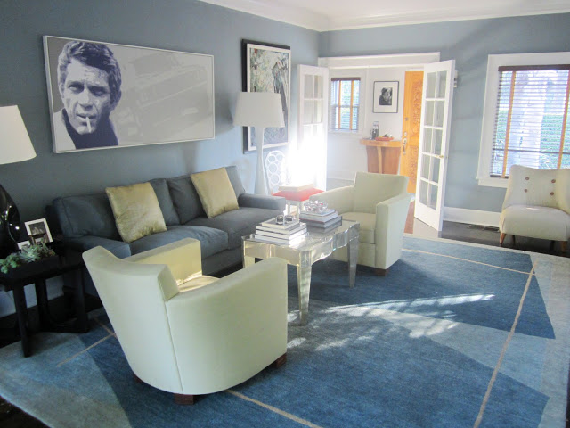 Blue living room with Steve McQueen painting, French doors, large area rug, cream colored arm chairs and a lucite coffee table