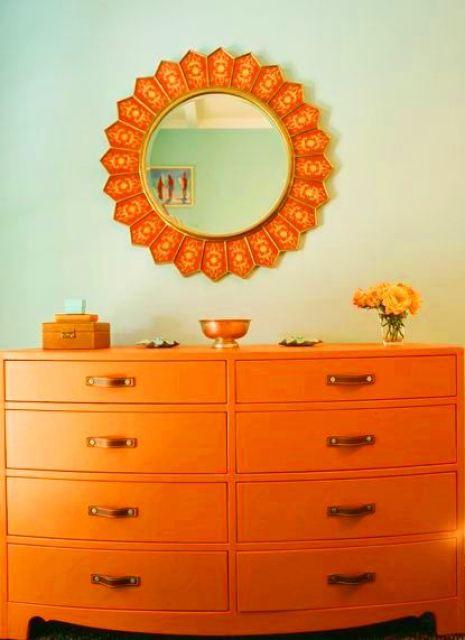 Orange chest of drawers under and orange sunburst mirror