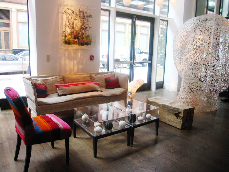 Chair with a curved back and spindle legs upholstered in a serape and an eclectic mix of furniture  and a steel sculpture of a head made of letters by Jaume Plensa in the Crosby Street Hotel Lobby