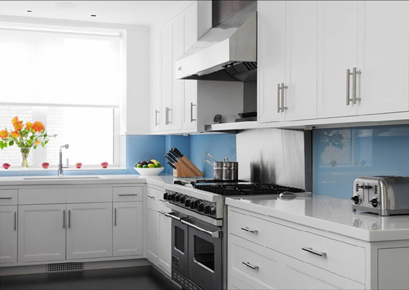 Retro kitchen with blue glass backsplash, white stone countertops, white recessed panel cabinetry and stainless steel appliances