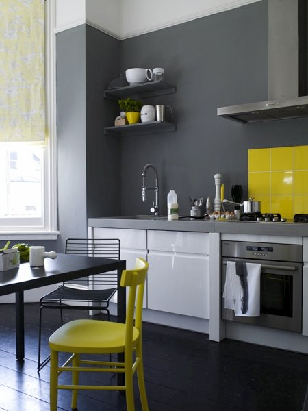 Modern kitchen with glossy white lower cabinets, dark wide plank wood floor, dark grey walls, a bright yellow chair and yellow tile backsplash