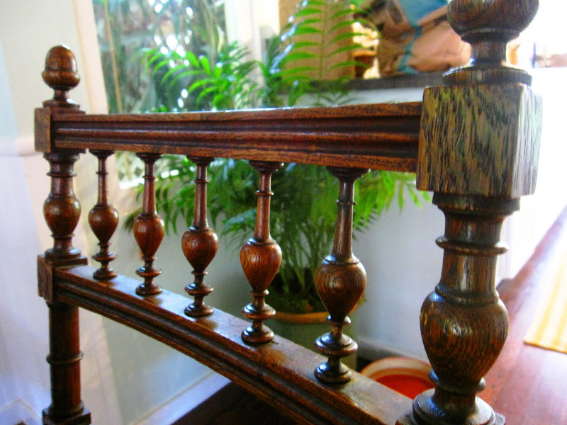 Close up of the carved details on an antique dark stained wood dining chair