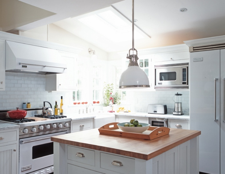 White kitchen with subway tile backsplash, pendant light, white Viking appliances and an island with butcher block countertop
